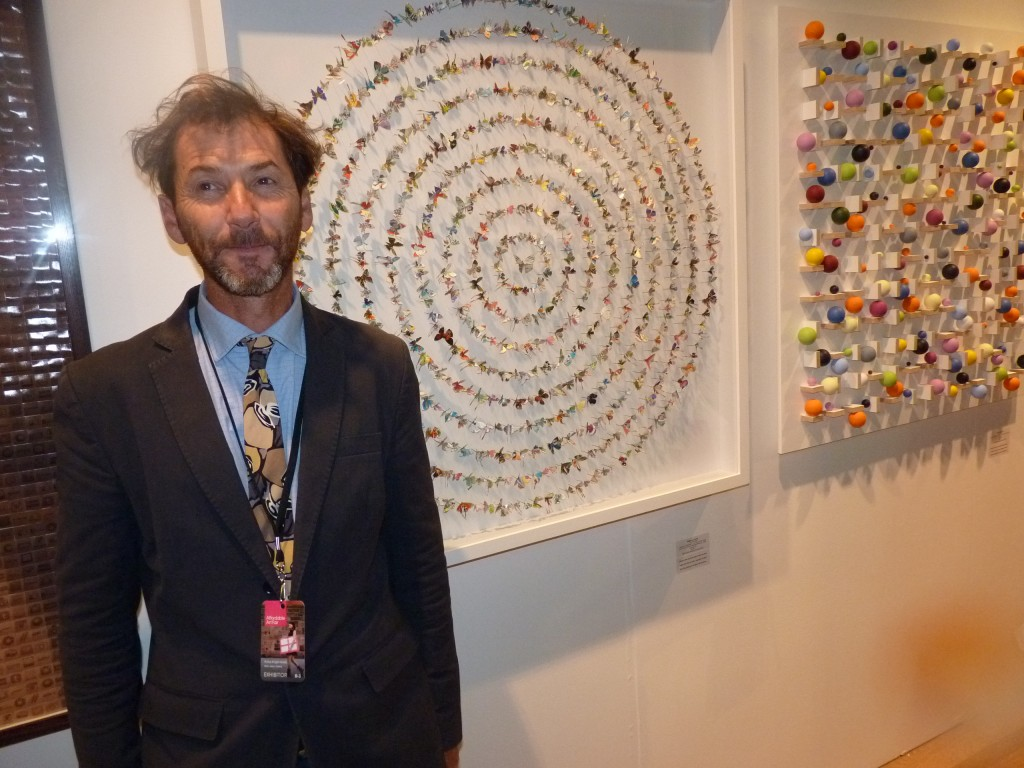Rufus Knight-Webb at Mark Jason Gallery from London stands in front of circles of butterflies cut out from postage stamps by Rebecca Coles (Stamps 198, 100x100cm, $5300 before tax), a line which sold ten copies by Sunday evening, with five more on order.  Beyond the Coles is the equally colorful Event 15, by Stuart Hartley, Acrylic on Birch Ply and Beech mounted on board, 100x100cm, $6500.