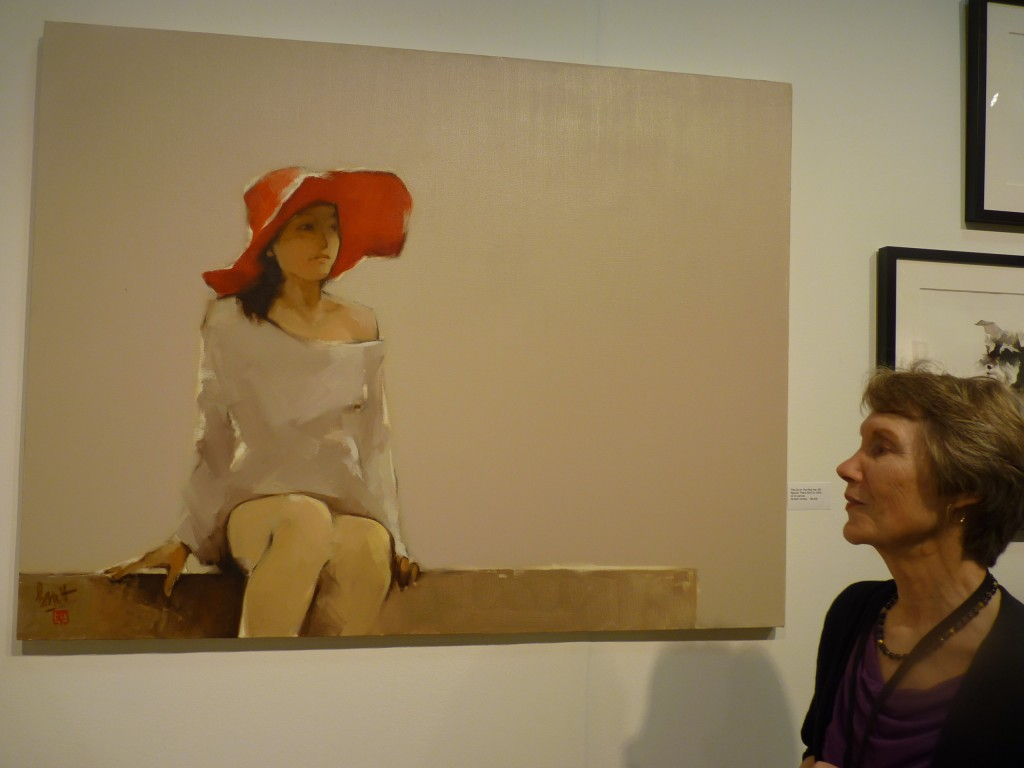 "Judith Hughes Day stands in front one of her most interesting prizes in the Vietnamese Contemporary Fine Art she offered (www.artnet.com/judithday.html), The Girl in the Red Hat by Nguyen Thanh Binh, 60, oil on canvas, 39.5"" x 51"", $6,400."